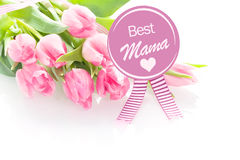 Mothers Day greeting - Best Mama. Heartwarming Mothers Day greeting - Best Mama - from a child on a round purple rosette with a gift of a bouquet of fresh pink royalty free stock photos
