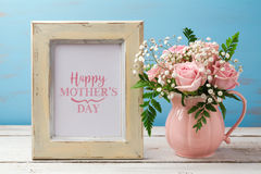 Mothers day greeting card with pink rose flower bouquet and photo frame. On wooden table Royalty Free Stock Images
