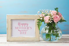 Mothers day greeting card with rose flower bouquet and photo frame. Over wooden background Stock Photography