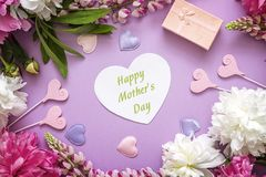 Mothers Day greeting message with peonies, gift box and decorative hearts on violet background. Top view. Happy mother`s day concept royalty free stock images