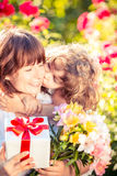 Mothers day. Happy women and child with beautiful spring flowers against green background. Family holiday concept. Mothers day Stock Photography