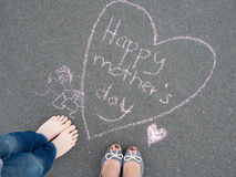 Mothers day - heart shape chalk drawing and the feet of a child. Mothers day - heart shape chalk drawing and the feet of a boy and the feet of his mother stock image