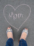 Mothers day - heart shape chalk drawing and the feet of a mother. With the text message mom stock image