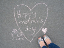 Mothers day - heart shape chalk drawing and the feet of a mother. Mothers day - heart shape chalk drawing with text message and the feet of a woman on the royalty free stock photo