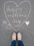 Mothers day - heart shape chalk drawing and the feet of a mother. Mothers day - heart shape chalk drawing with text message and the feet of a woman on the stock image