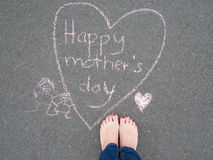 Mothers day - heart shape chalk drawing and the feet of a woman. On the asphalt ground stock images