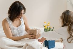 Mothers day. Little daughter keeps gift and flowers for her mother. Background interior of bedroom, mother in bed, morning royalty free stock photo