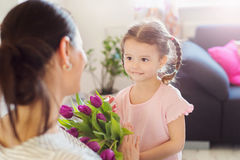 Mothers day, little girl giving flowers to her mum Stock Photo