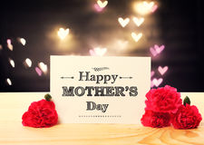 Mothers Day message card with carnation flowers. And heart shaped lights royalty free stock photo