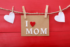 Mothers day message with clothespins over red wooden board. Mothers day message with felt hearts hanging with clothespins over red wooden board royalty free stock images