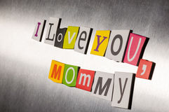 Mothers day message of color magazine letter clippings on metal background. I love you mom or mommy. Selective focus.  Royalty Free Stock Image