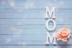 Mothers day message with rose flower on a blue wooden table. Pla Stock Photography