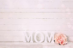 Mothers day message with rose flower on white wooden background. Royalty Free Stock Images
