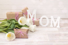 Mothers day message with white tulips and gift boxes on white wo Stock Photo