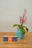 Mothers day. Mom spelled with colorful alphabet block displayed with a small pink flowers in a blue vase on a table Stock Photo