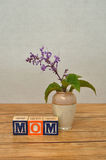 Mothers day. Mom spelled with colorful alphabet block displayed with a small purple flowers in a vase on a table Stock Images