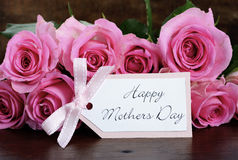 Mothers Day pink roses on rustic dark wood table. Stock Image