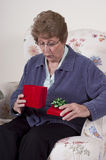 Mothers Day Present Grandma Birthday Gift Surprise. Senior mature woman has look of shock and surprise as she receives a surprise gift for Mothers Day or another Royalty Free Stock Photography