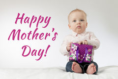Mothers day. Serious baby boy holding some present in his arms. Thoughtful infant kid with a gift. Ready postcard Royalty Free Stock Photos