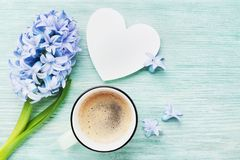 Mothers Day spring greeting background with hyacinth flowers, cup of coffee and white wooden heart top view. Morning breakfast. stock photography