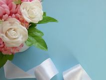 Bouquet of roses, silk ribbon on blue background. stock photography