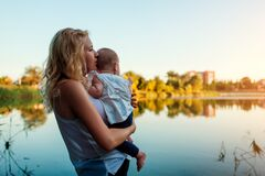 Free Mothers Day. Young Woman Holding And Hugging Baby Girl By Spring River. Family Walking Outdoors. Kid Exploring World Stock Image - 180161251