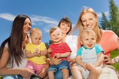 Mothers holding cute babies sitting together royalty free stock image