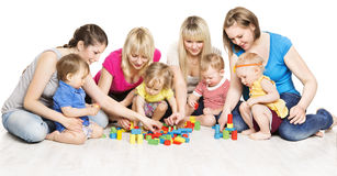 Mothers and Kids Group Playing Toys, Mother Play with Baby. Mothers and Kids Group Playing Toys, Mother with Baby Play Building Blocks over White Background Royalty Free Stock Images