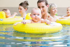 Mothers and kids having fun together playing with toys in pool Royalty Free Stock Image