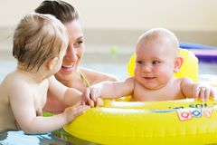 Mothers and kids having fun together playing with toys in pool Royalty Free Stock Images