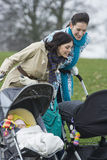 Mothers Looking In Strollers At Park Stock Image