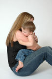 Mothers Love. A mother hugs her baby child to calm him down while sitting on the floor Stock Photo