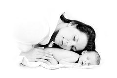 Mothers love. Loving mother puts head on her sleeping newborn Royalty Free Stock Images