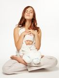 Mothers meditation. Mother meditating sitting in lotus yoga pose with little baby Royalty Free Stock Images