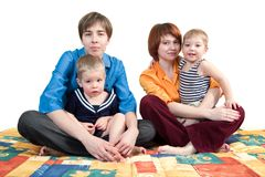 Mothers and sons. Two young mothers with small sons sitting on the sofa stock image