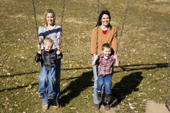 Mothers and sons on swing Stock Photography