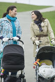 Mothers With Strollers In Park Having Chat Stock Photos