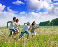 Mothers with teenagers running in meadow Stock Image