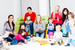 Mothers and children. Mothers with their children in the room. Women are talking and toddlers are playing Stock Image
