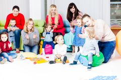 Mothers and children. Mothers with their children in the room. Women are talking and toddlers are playing Royalty Free Stock Images
