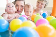 Mums and babies having fun at infant swimming course. Mothers and their kids having fun at baby swimming lesson between lots of water balls stock photography