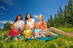 Mothers with their toddlers sitting in the meadow. Mothers with their toddlers sitting together on the green grass during wonderful summer day Stock Photo