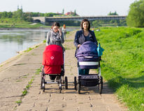 Mothers walk next to river Stock Image