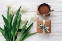 Mothers or womens day. stylish craft present with morning coffee. And tulips on white wooden rustic background. flat lay with flowers with space for text. hello Stock Images