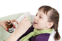 Mothre giving spoon dose of medicine to child. Mothre hand giving spoon dose of medicine liquid drinking syrup to child over white Stock Photos