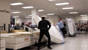 Motie die van arbeider nieuwe matras voor verkoop binnen de Baaiopslag bewegen stock video