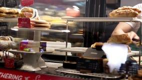 Motie die van barista voedsel voor klant nemen stock video