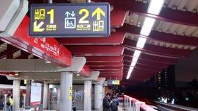 Motie die van MRT door platform bij nacht met richtingsteken overgaan op plafond stock videobeelden