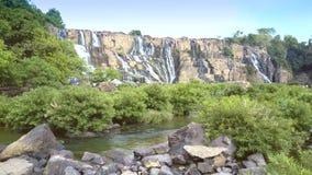 Motie langs rivier om zittingsachtereind op steen door waterval te koppelen stock footage