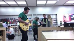 Motie van arbeider het spelen gitaar binnen Apple-opslag stock footage